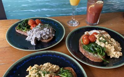 Plates of brunch with roasted cherry tomatoes, spinach and scrambled egg. Served with a glass of mimosa and Bloody Mary.