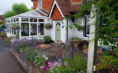 The front of The Crown Inn Dial Post pub with patio seating and a conservatory and a raised flower bed at the front. The pub is white washed with red tilled gables and roof and a sage green front door.