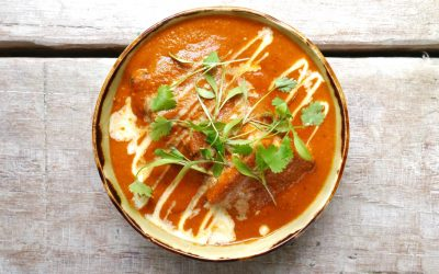 Overhead shot of a bowl filled with a bright orange, creamy tomato based curry garnished with herbs and drizzled with cream.