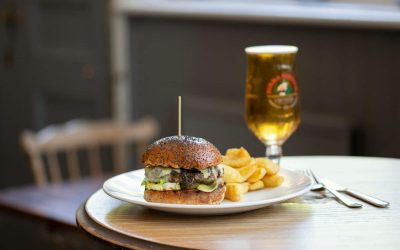 burger in chips on plate sever with glass of beer