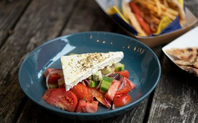 feta cheese, tomatoes and onion served as salad in dark blue plate
