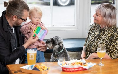 parents at the table with their child playing with toy and dog sitting, they are having fries and glass of beer