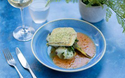 Pan fried herb crusted hake, tomato & shellfish 'kakavia' sauce and summer vegetables.