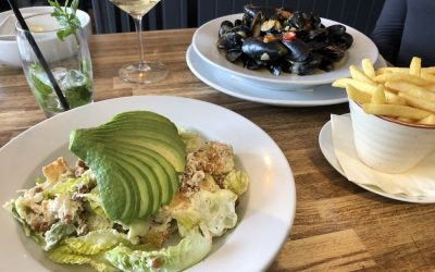 Plates of food laid out on a wooden table with a sliced avocado salad, moules mariniere and fries.