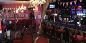 Interior of the Regency Tavern, plush red wallpaper, gold gilded furniture and frames