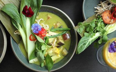 Green curry decorated with pak choi and edible flowers.