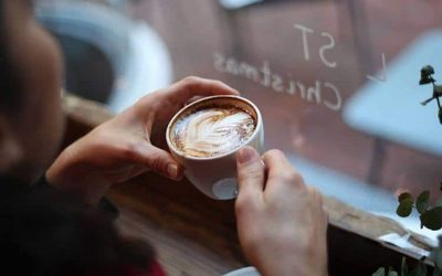 A pair of hands holding a latte, the person is sat looking out a window