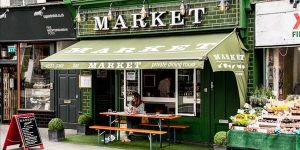 Outside of market in Hove with the green paintwork and alfresco dining