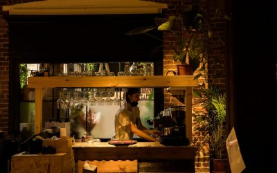 Barista preparing a coffee behind the bar with warm lighting and red brick walls.
