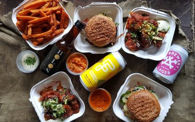 Takeaway boxes of sweet potato fries, cauliflower wins, burgers, dipping sauces and cans of beer.