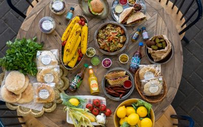 table laid out with colorful food including corns,lemons, hummus, pitta bread, garlic
