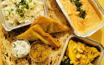 Overhead picture of takeaway curry, three foil containesrs two samosas, a naan and chutney