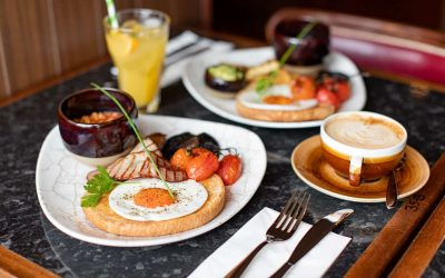 A table laid out with two large Full English breakfasts coffee and juice
