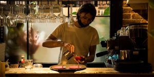 Barista making a coffee at the bar with warm lighting and red brick wall