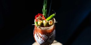 A glass of Bloody Mary garnished with olives, fresh chilli and herbs