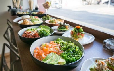 A variety of poke bowls and plates of sushi served on the table.