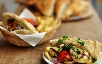 A basket of bread and fries alongside a side plate of artichokes and houmous